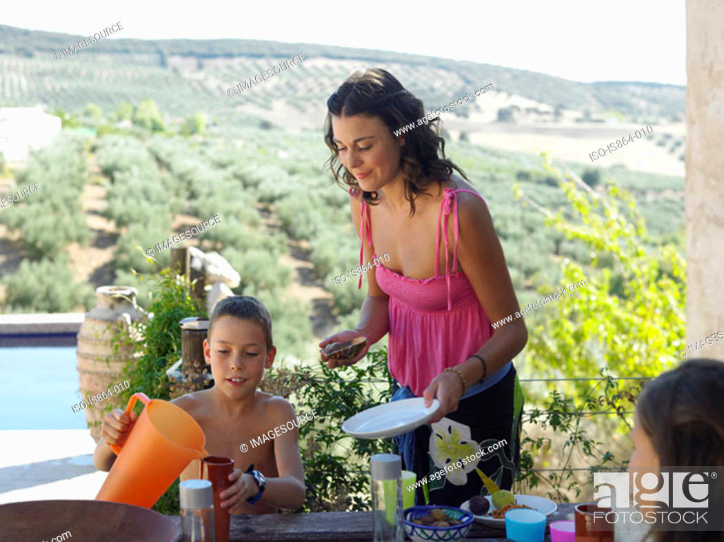 Stock Photo: Woman and children having meal outdoors.