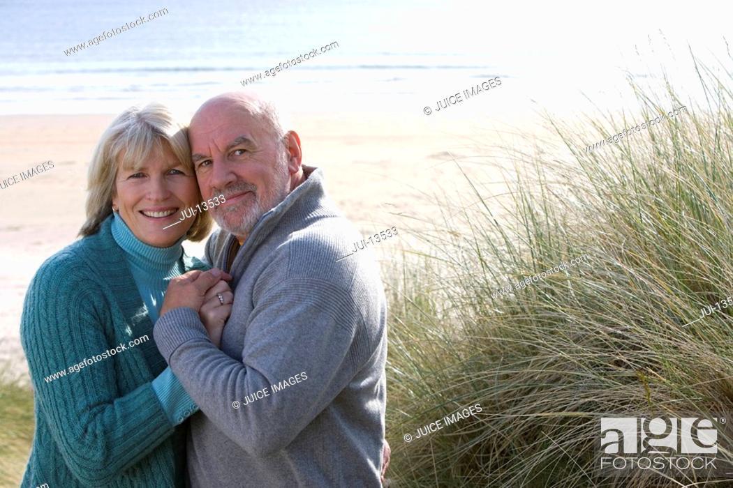 Stock Photo: Senior couple embracing on beach, smiling, portrait.