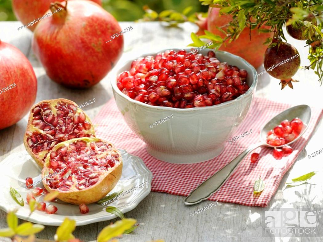 Stock Photo: Spooning the seeds out of a pomegranate.