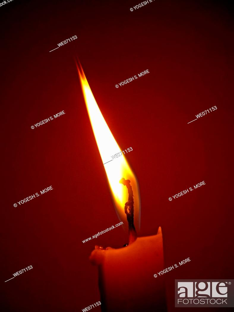 Stock Photo: Flame of a candle in the darkness.