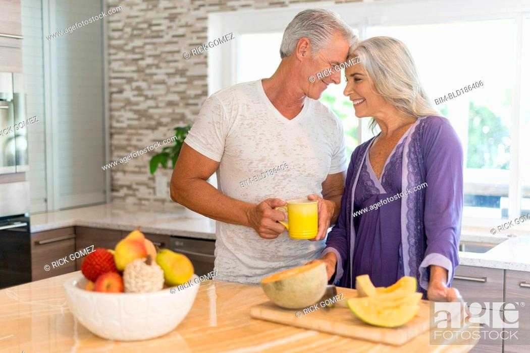 Stock Photo: Caucasian couple touching foreheads in kitchen.