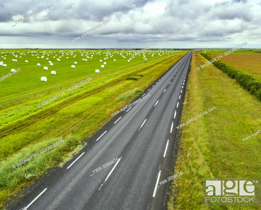 Photo de stock: Hay bales and empty road, summertime, South Coast, Iceland.