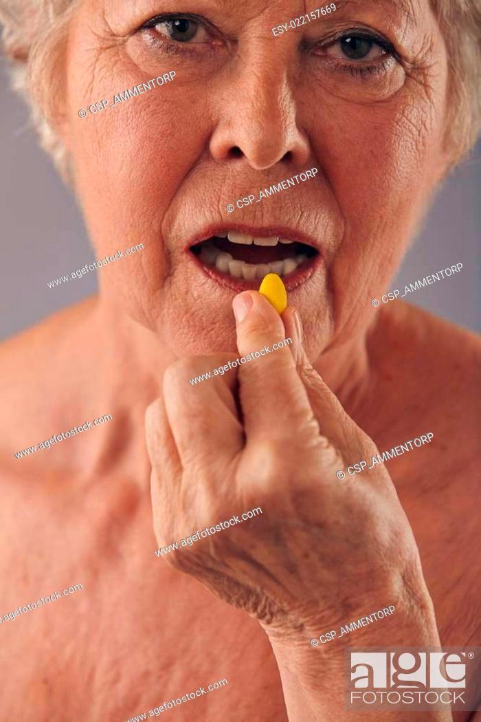 Stock Photo: Mature woman talking medicine pill.