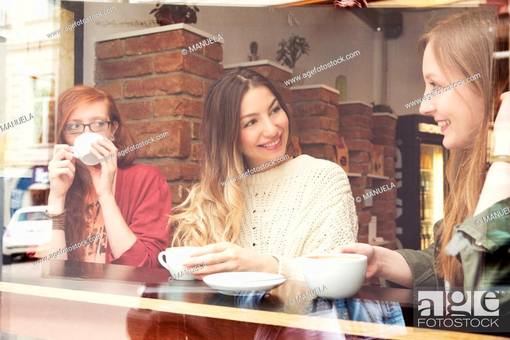 Stock Photo: Young women chatting over coffee in cafe.