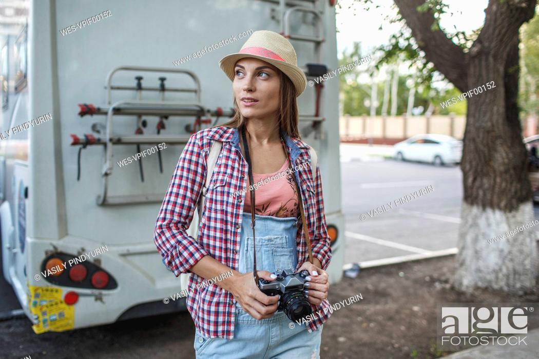 Stock Photo: Young woman with a camera on car park looking around.