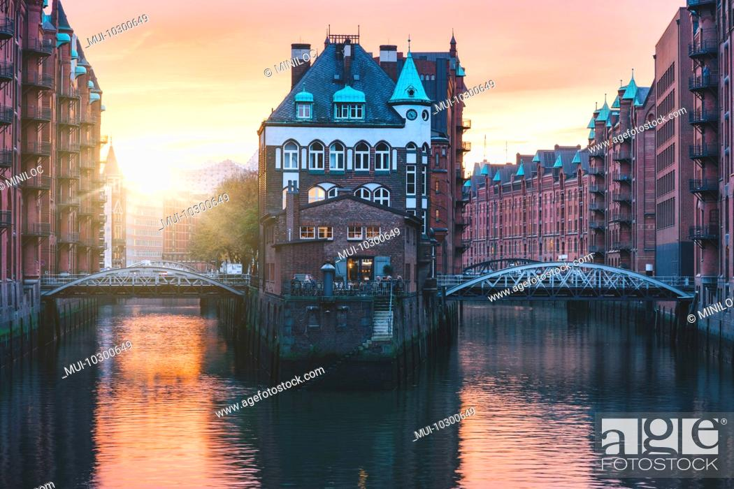 Stock Photo: Hamburg city old port, Germany, Europe. Historical famous warehouse district with water castle palace at sunset golden light.