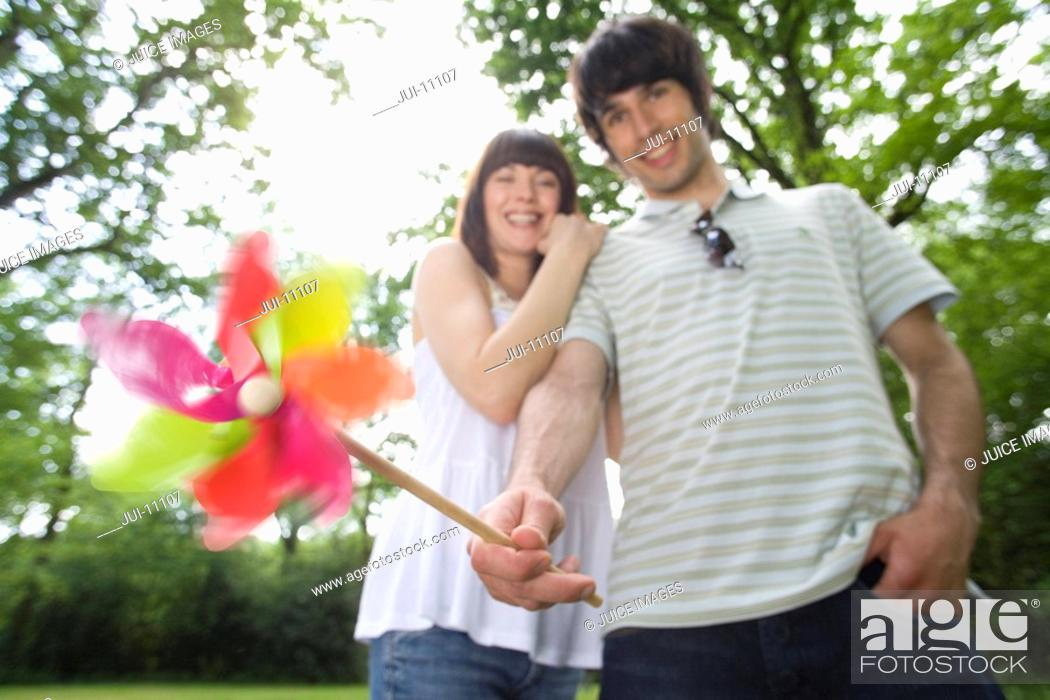 Stock Photo: Close-up of windmill held by 20's couple out of focus in background in leafy countryside ,.