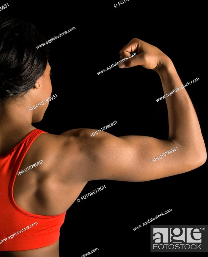 Stock Photo: Back view of African American woman flexing muscular bicep.