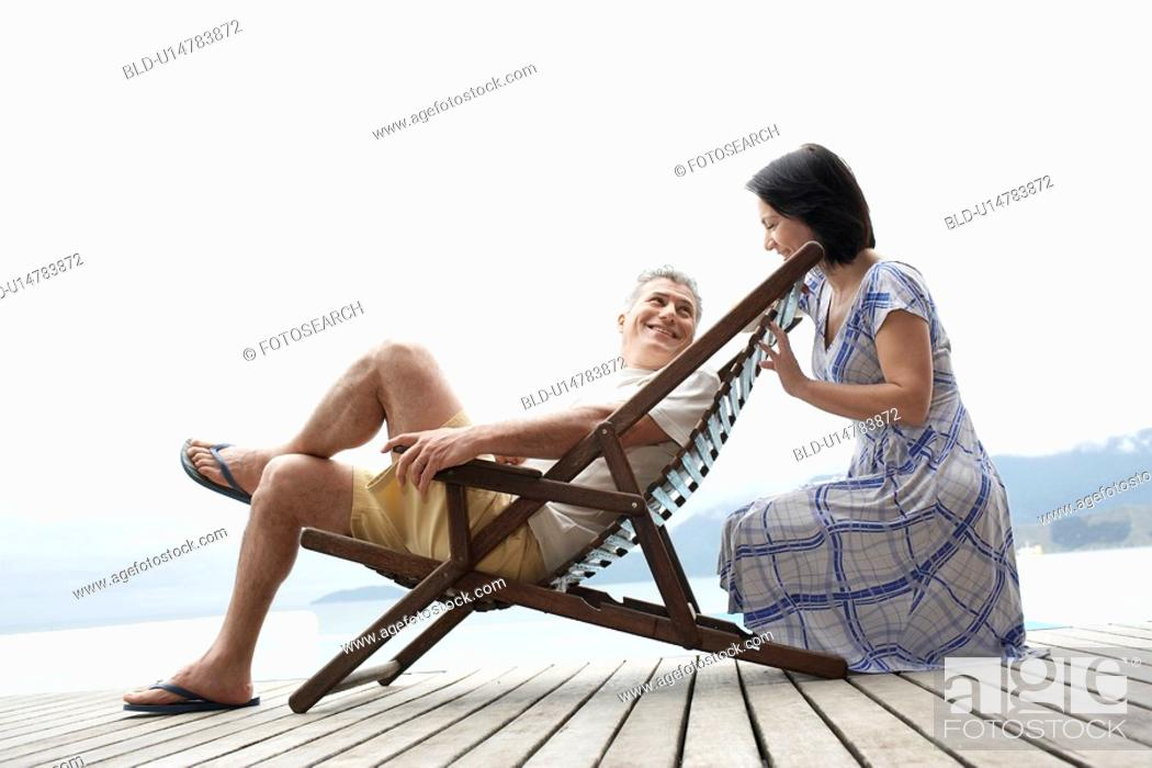 Stock Photo: Mature couple relaxing on deck.