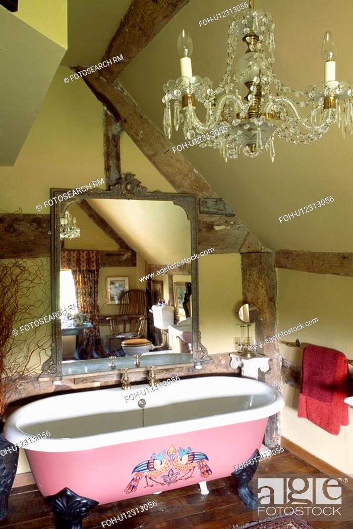 Large antique mirror above painted clawfoot bath in cream attic ...