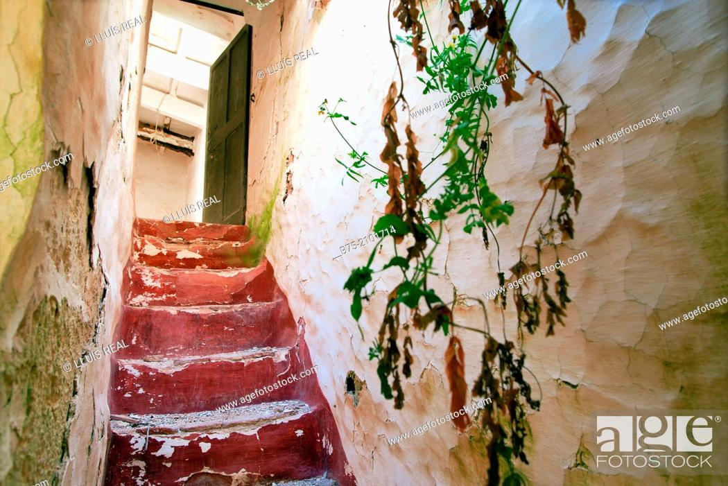 Stock Photo: Staircase with open door to the end in an abandoned house, Menorca, Balearic Islands, Spain.