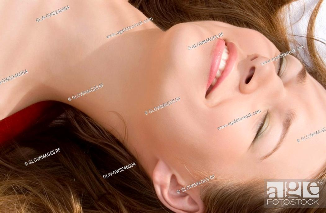 Stock Photo: Close-up of a young woman smiling with her eyes closed.