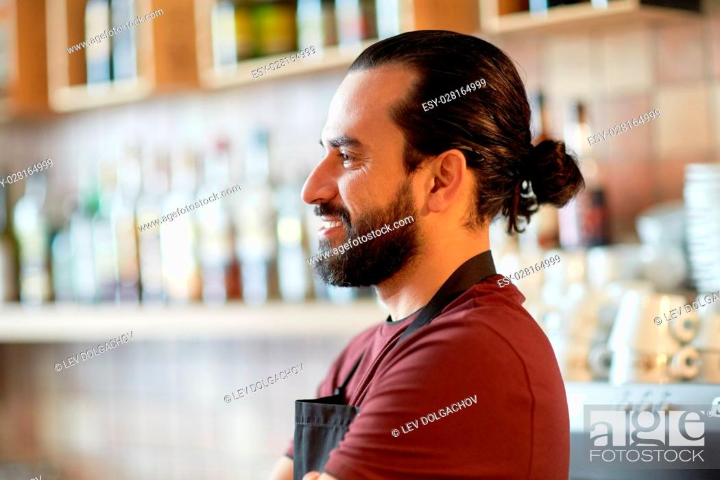 Stock Photo: small business, people and service concept - happy man or waiter in apron at bar or coffee shop.