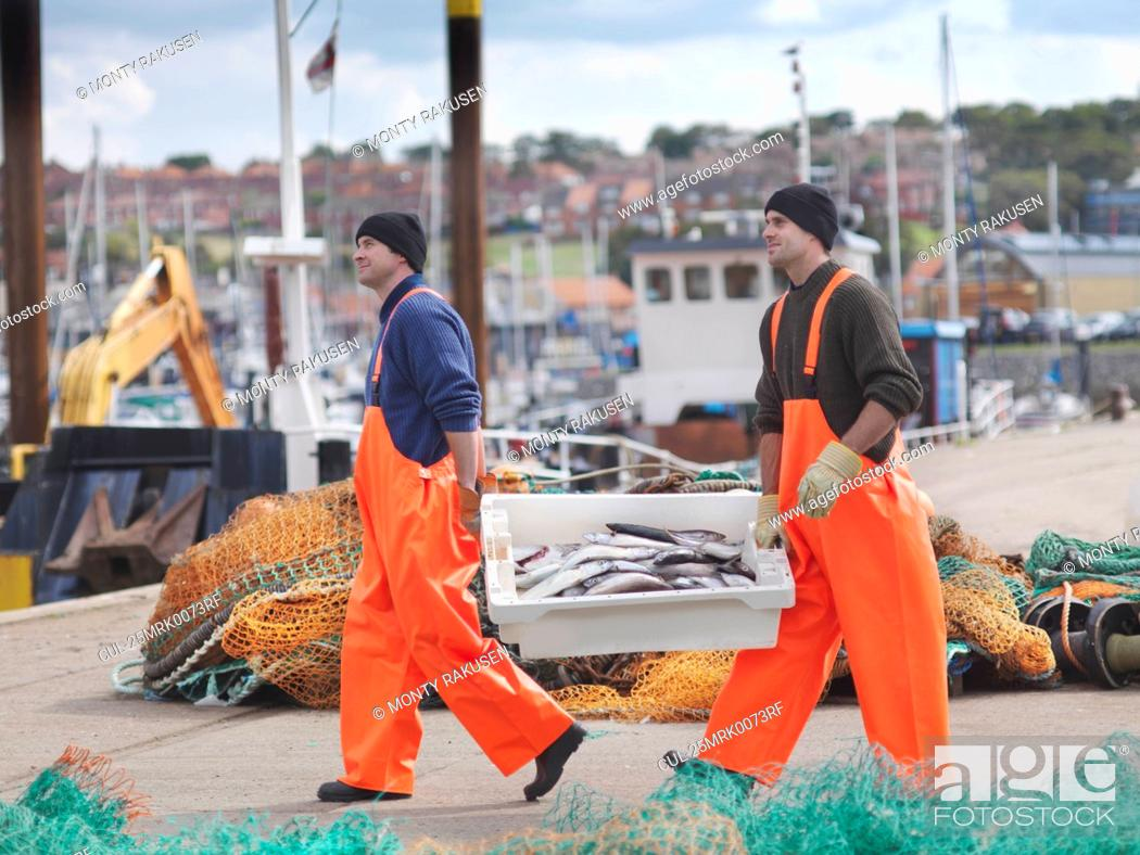 Stock Photo: Fishermen with box of fish on harbour.