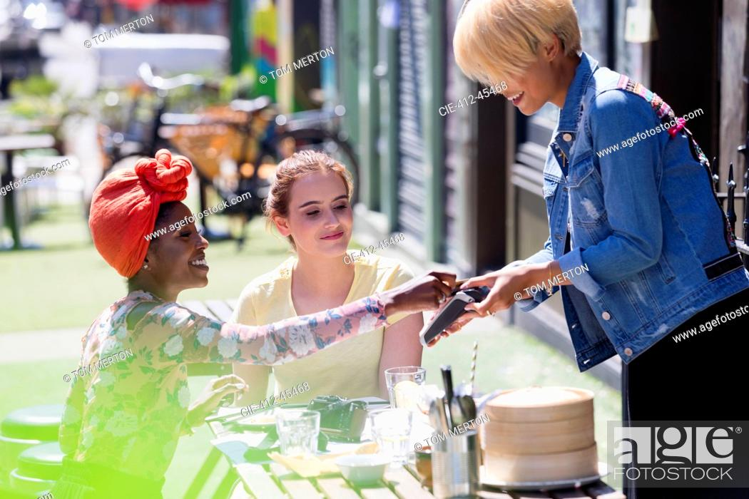 Stock Photo: Young woman paying waitress with credit card at sunny sidewalk cafe.
