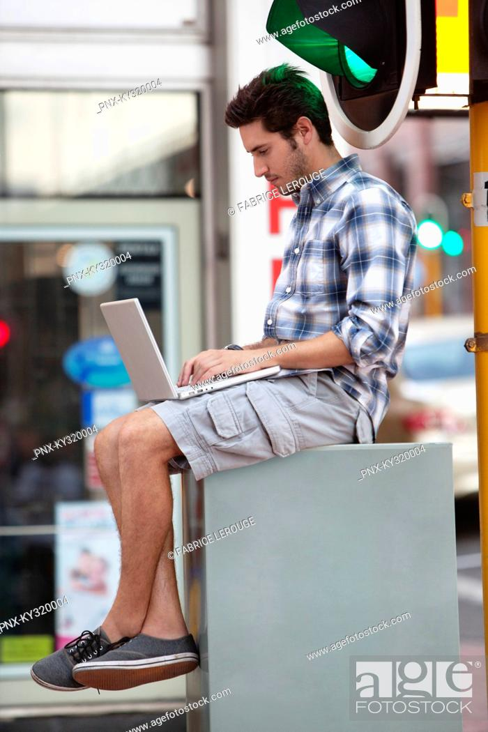 Stock Photo: Man using a laptop near traffic light.