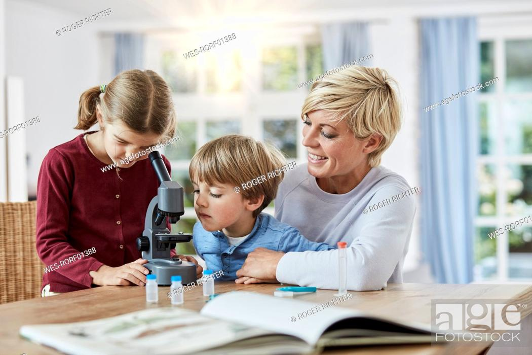 Stock Photo: Mother with daughter and son using microscope at home.