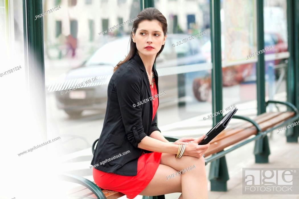 Stock Photo: Woman sitting at a bus stop.