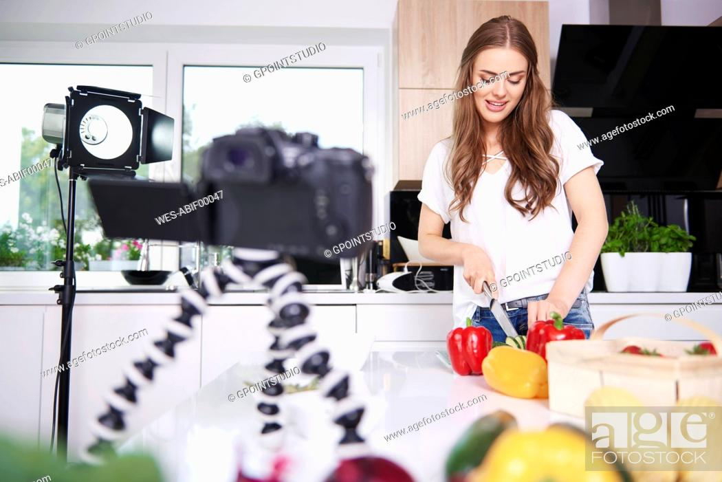 Stock Photo: Woman recording while chopping vegetables.