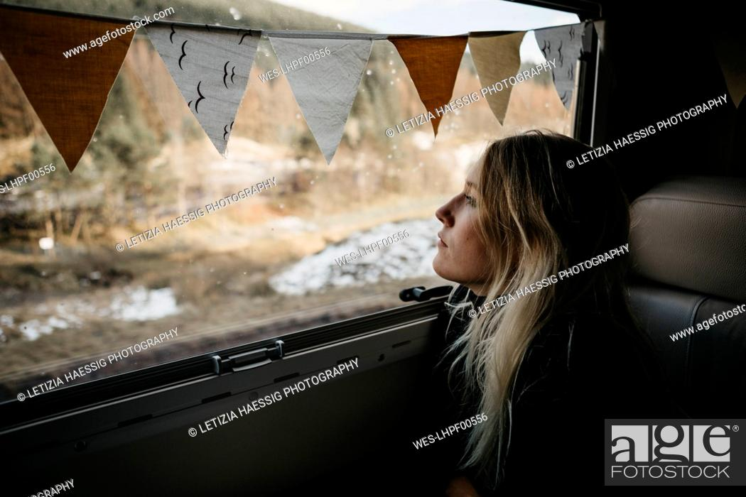 Photo de stock: Pensive young woman looking out of car window.