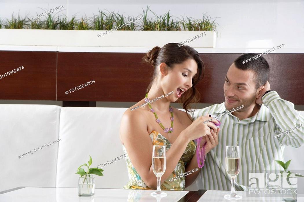 Stock Photo: Woman opening gift next to boyfriend.