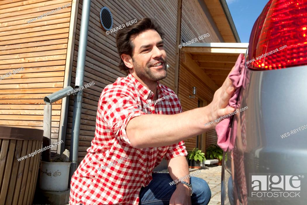 Stock Photo: Germany, Bavaria, Nuremberg, Mature man cleaning car in front of house.