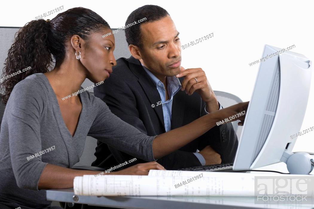 Stock Photo: Partners working on computer together in office.