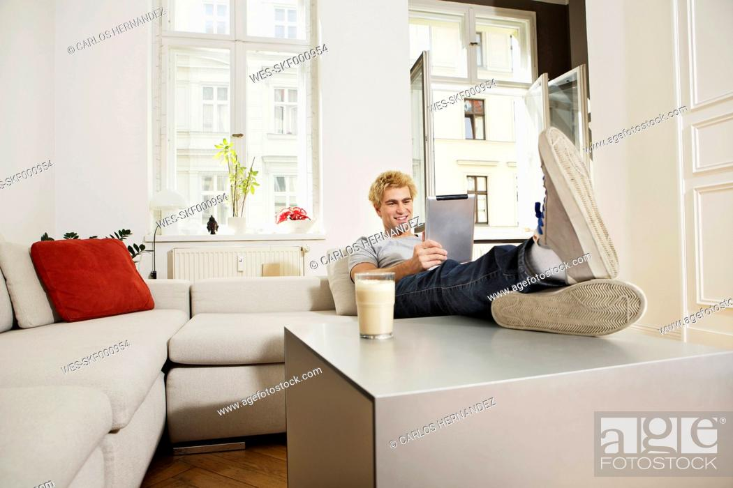 Stock Photo: Germany, Berlin, Young man using digital tablet, smiling.