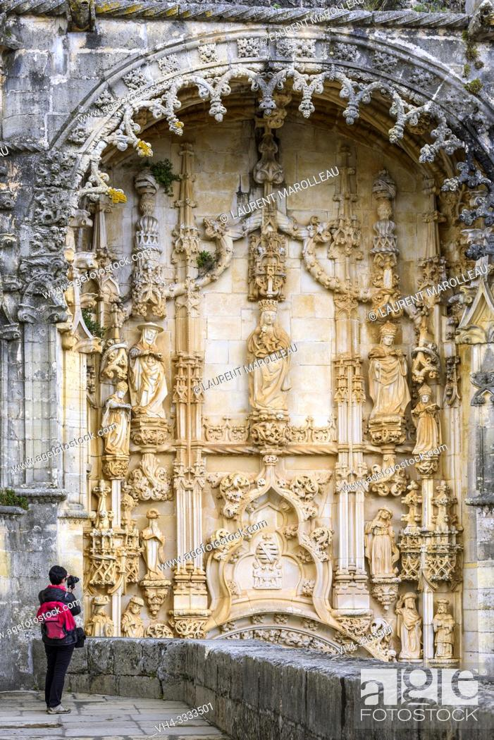 Stock Photo: (Model Release) Woman taking a picture of Tympanum (with figures of the Christian religion), Portal of the Manueline church, Convent of Christ in Tomar.