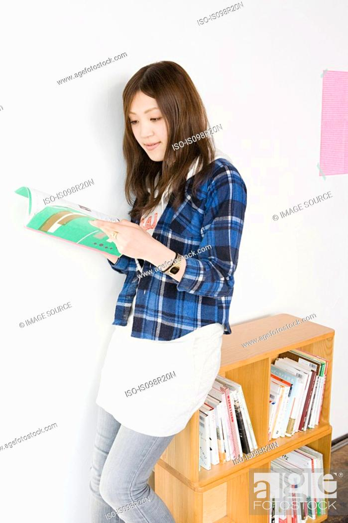 Stock Photo: Young woman looking at design book.