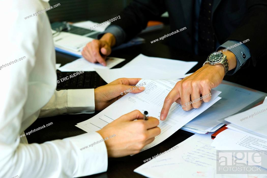 Stock Photo: Person signing paperwork, cropped.