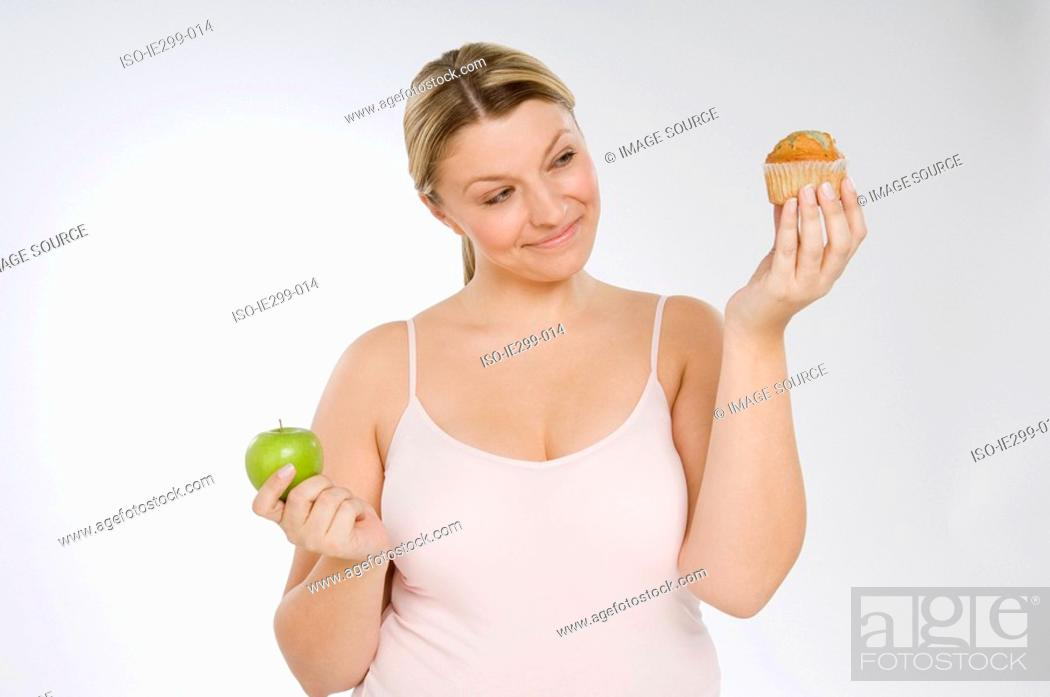 Stock Photo: A woman deciding between a muffin and an apple.