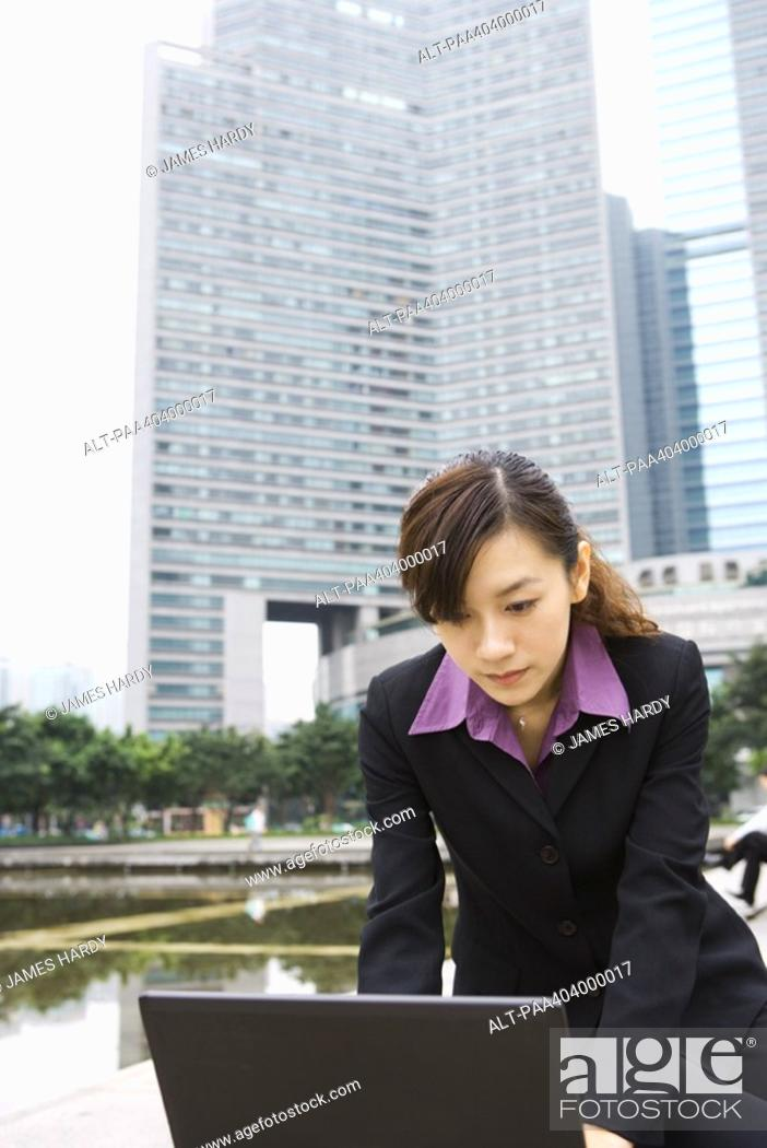 Stock Photo: Young businesswoman using laptop in office park.