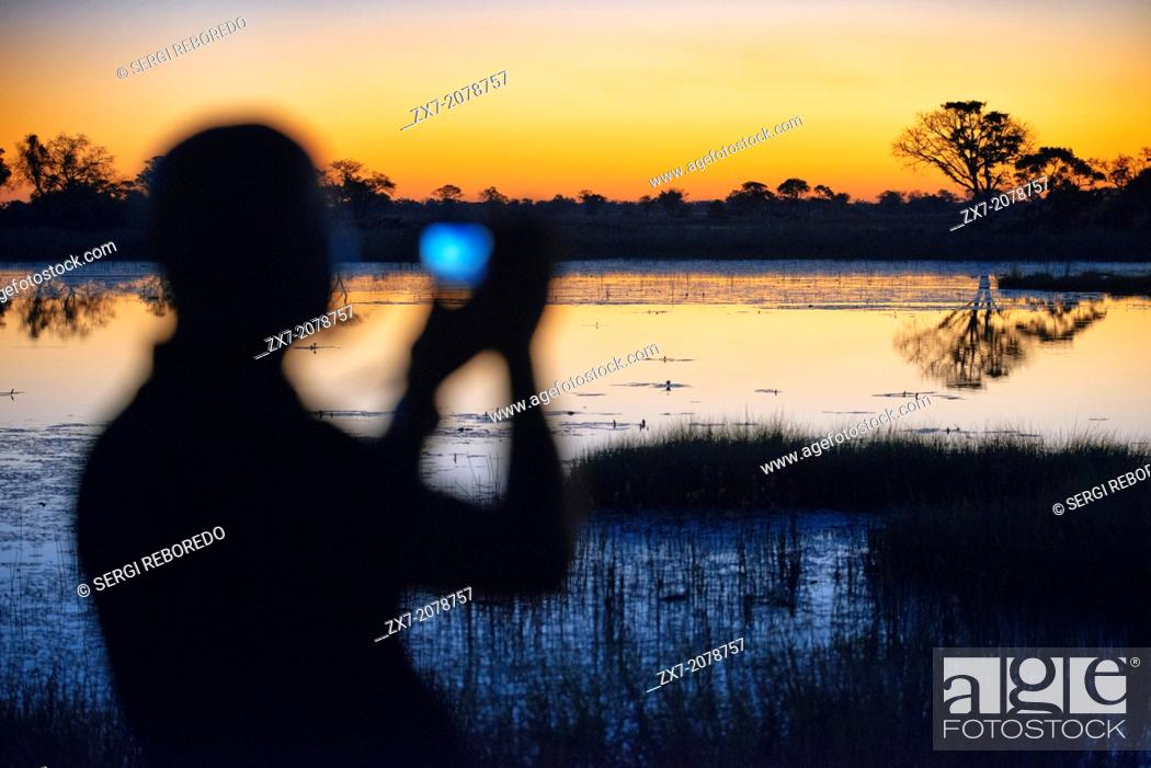 Stock Photo: A man with binoculars enjoy the best sunsets in the Okavango Delta Eagle Fish Eagle Island Camp Bar Camp Orient Express.