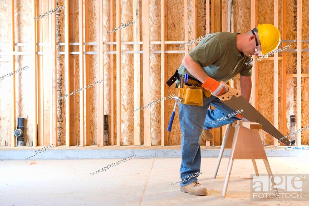 Stock Photo: Builder in hardhat sawing, side view.