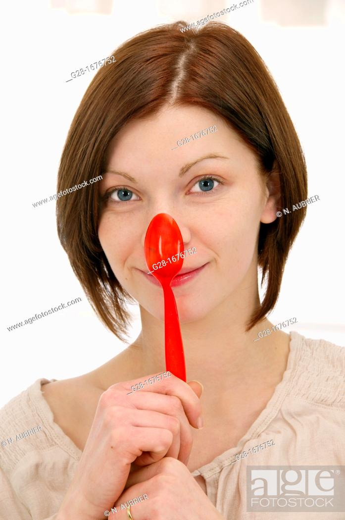 Stock Photo: young smiling woman in beige, holding a red plastic teaspoon over her nose.