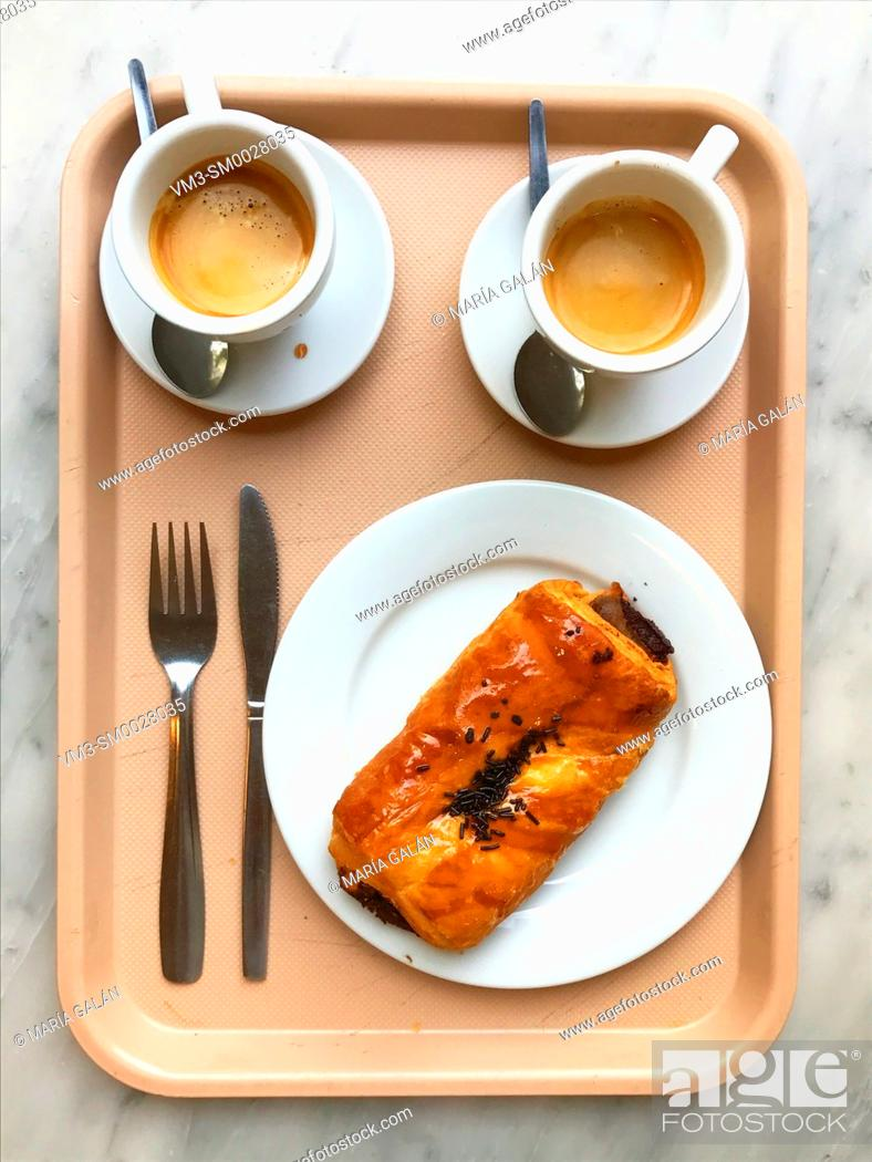 Stock Photo: Two cups of coffee and chocolate napolitana cake on a tray. View from above.
