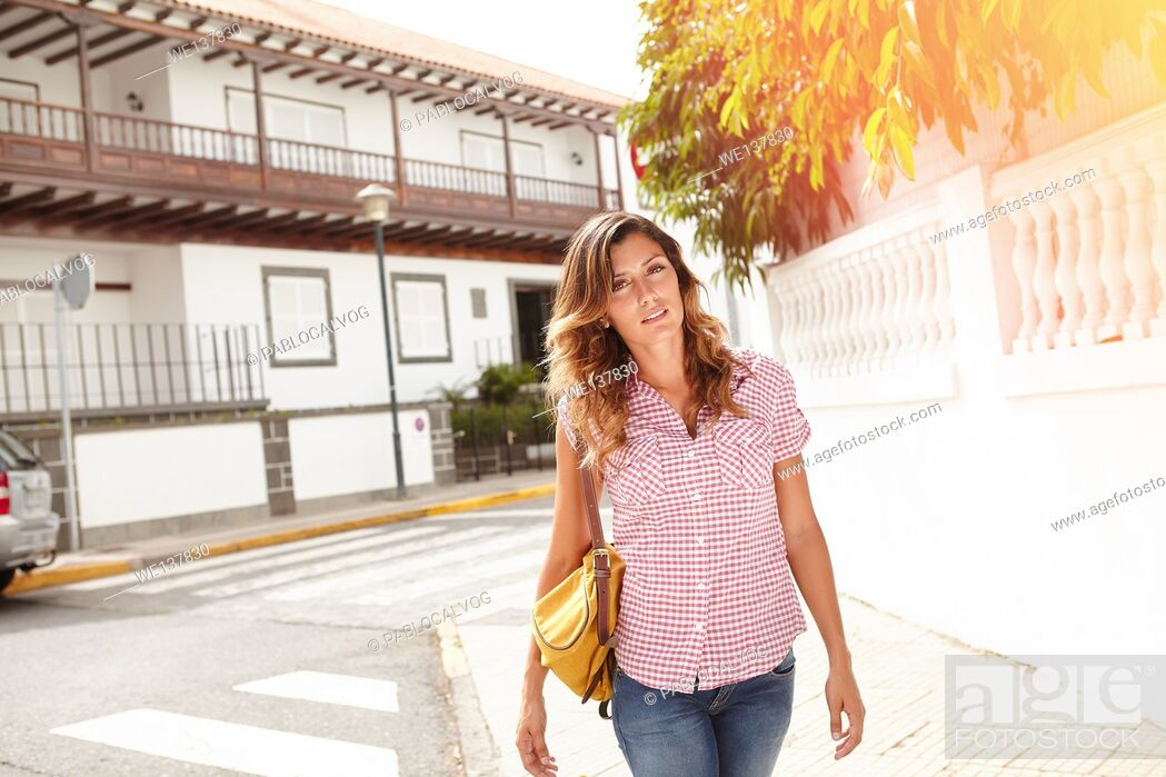 Stock Photo: Beautiful young woman 20-24 years old walking down the street and looking at the camera.