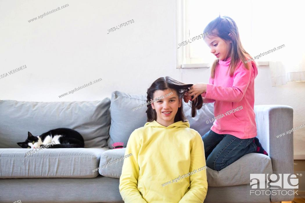 Stock Photo: Little girl braiding her sisterƒ.s hair.