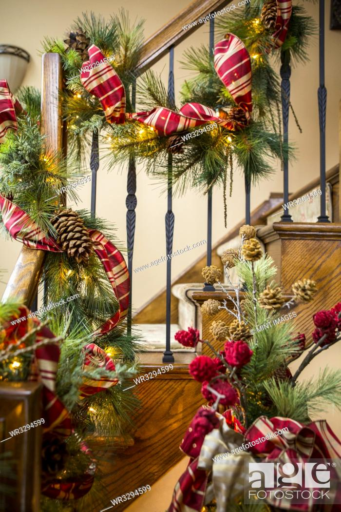 Stock Photo: Banister decorated with boughs and string lights for Christmas.