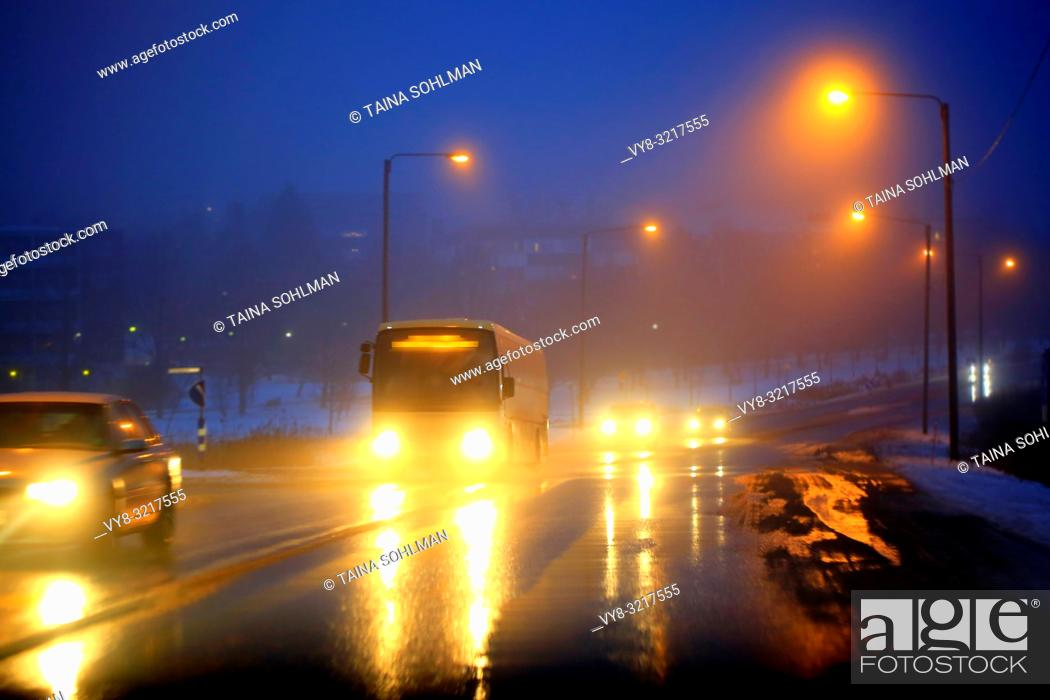 Stock Photo: Headlights of cars and a coach bus reflect on wet road on a foggy, blue winter evening in a suburban area. Salo, Finland.