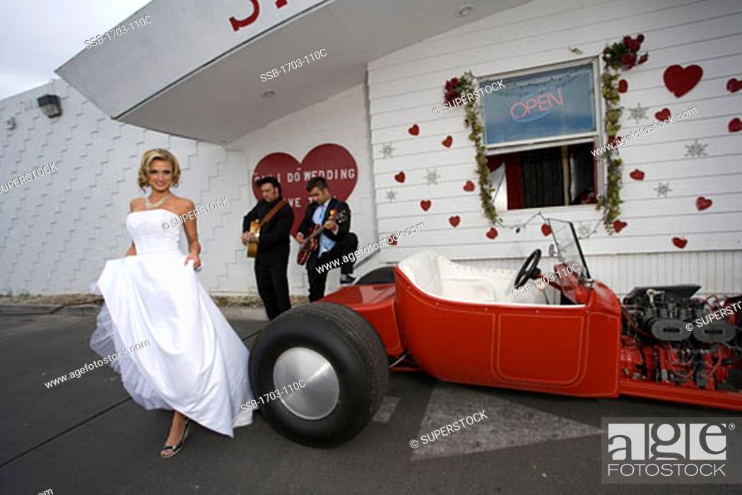 Bride Standing Beside A Convertible Car At A Drive Thru Wedding
