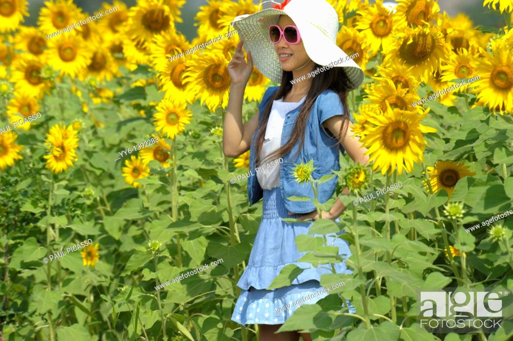 Stock Photo: girl with hat , sunflower fields of lopburi , central Thailand.