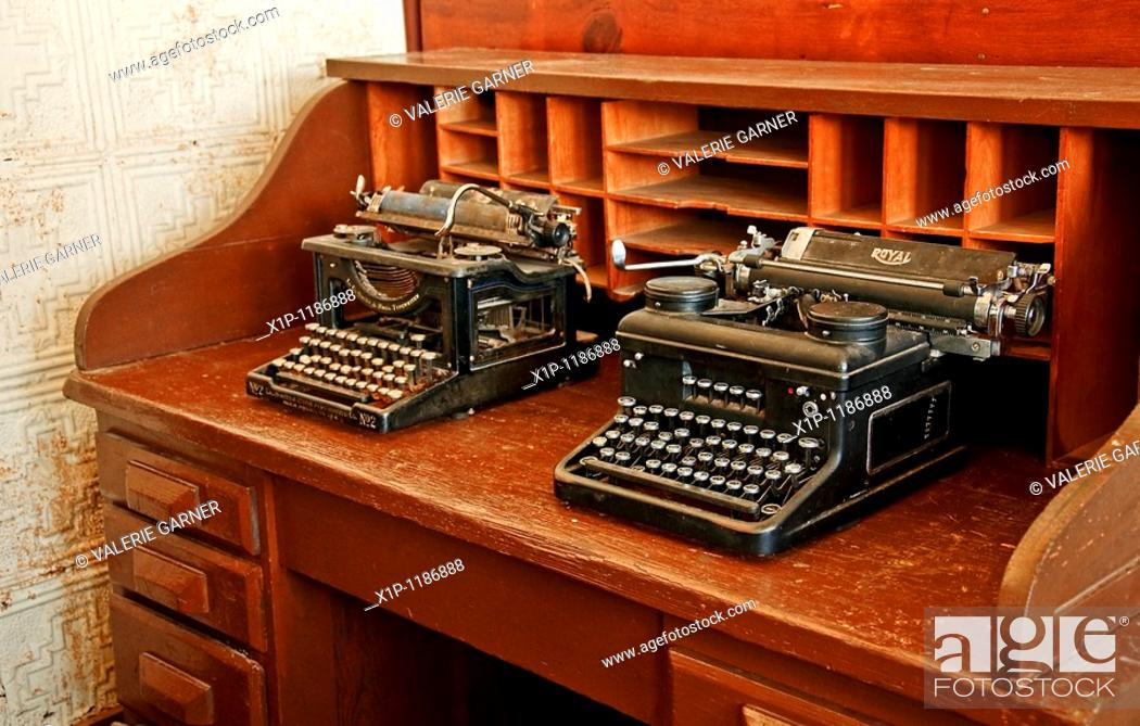 Stock Photo: These two antique black typewriters are sitting on a vintage turn of the century wooden desk, along with vintage wall paper in the background for this past era.