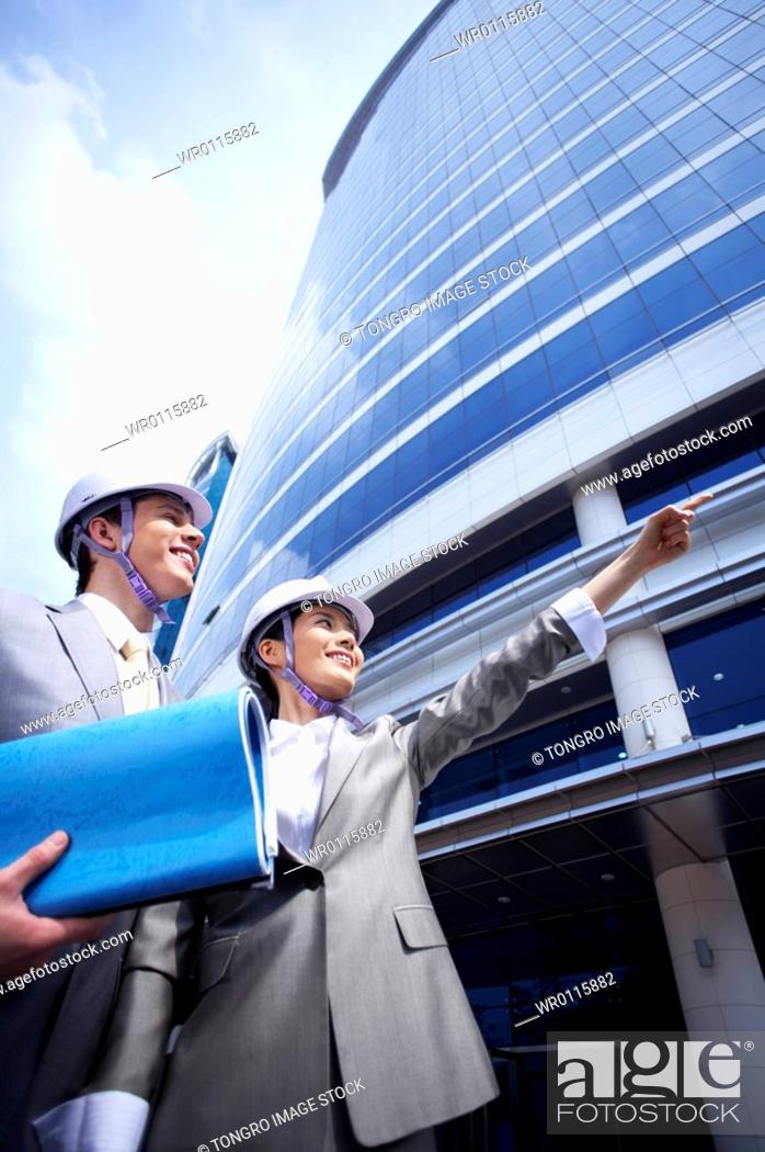 Stock Photo: man and woman with safety helmet on pointing out distant place.