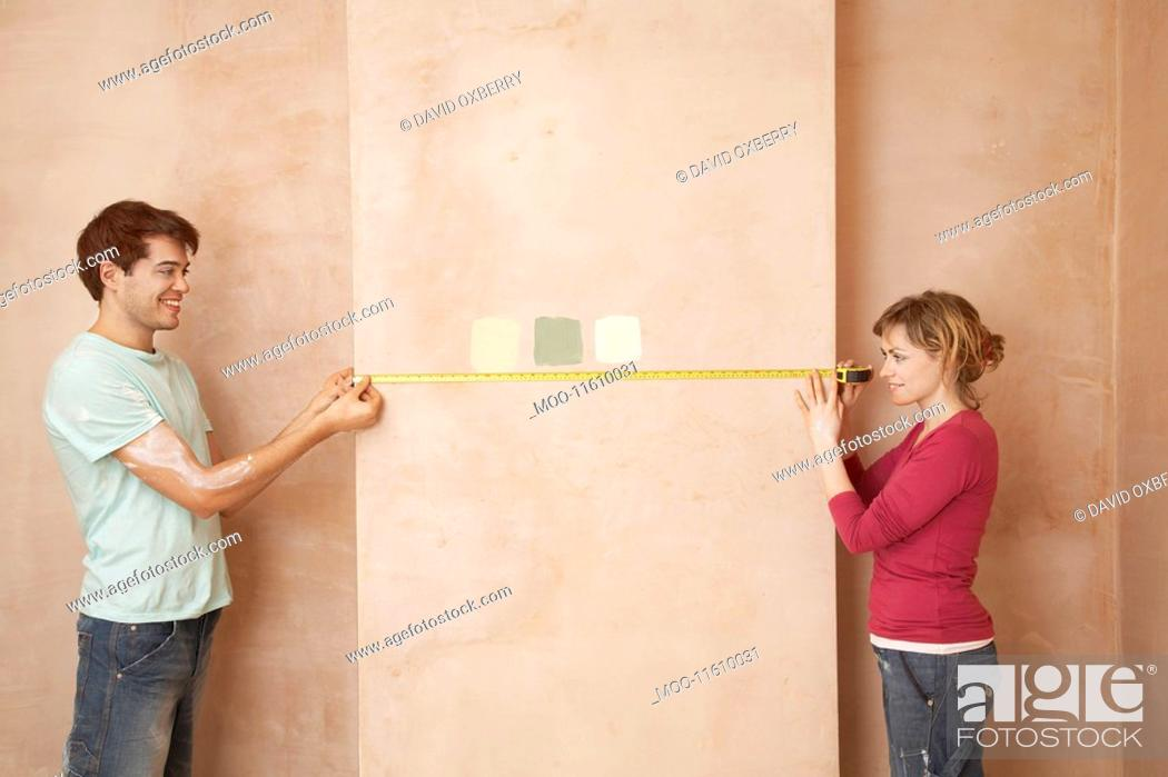 Stock Photo: Couple holding measuring tape to wall in unrenovated room.