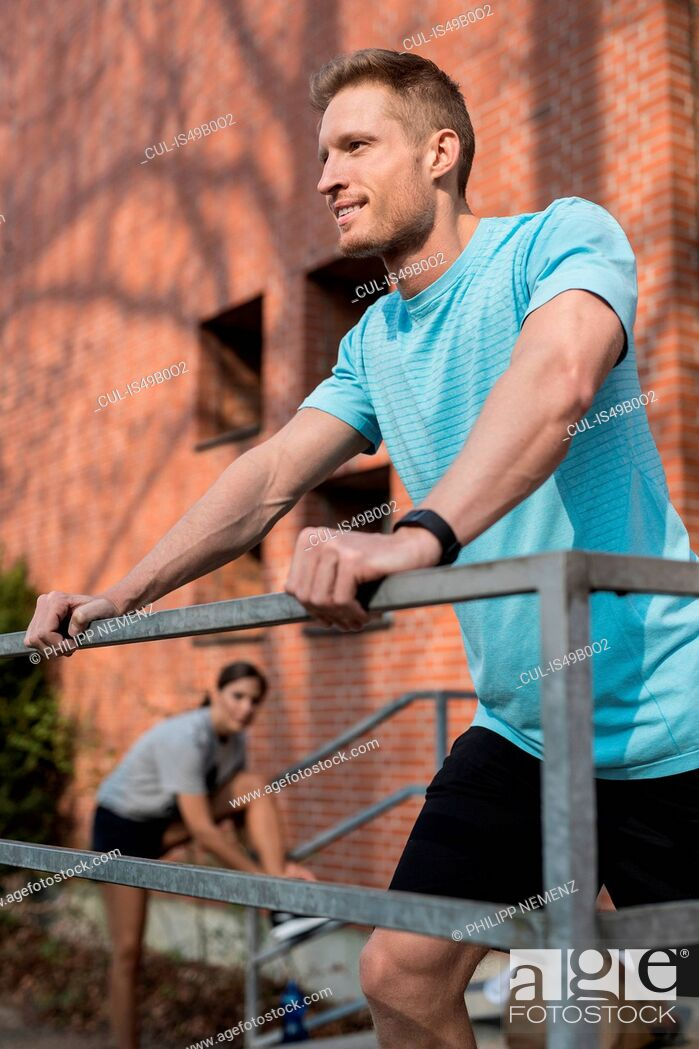 Stock Photo: Young man wearing sports clothing, leaning on railing, young woman tying shoelaces in background.