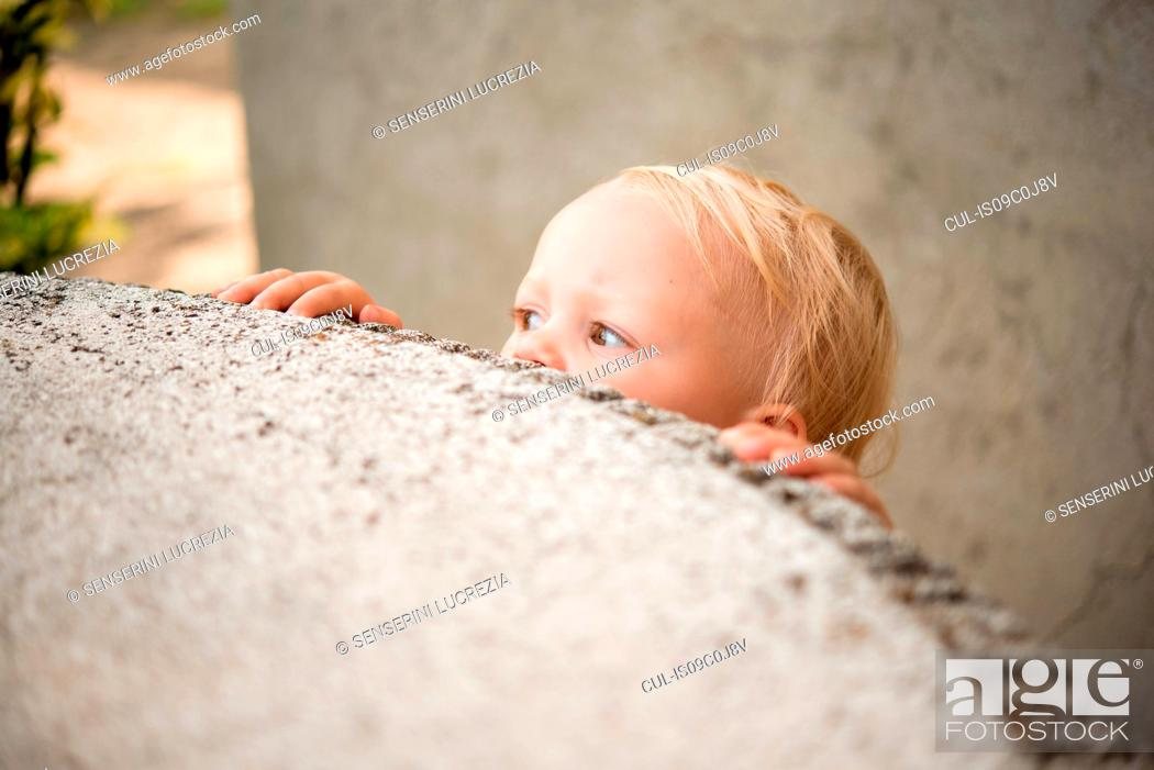 Stock Photo: Cute female toddler peering over wall.