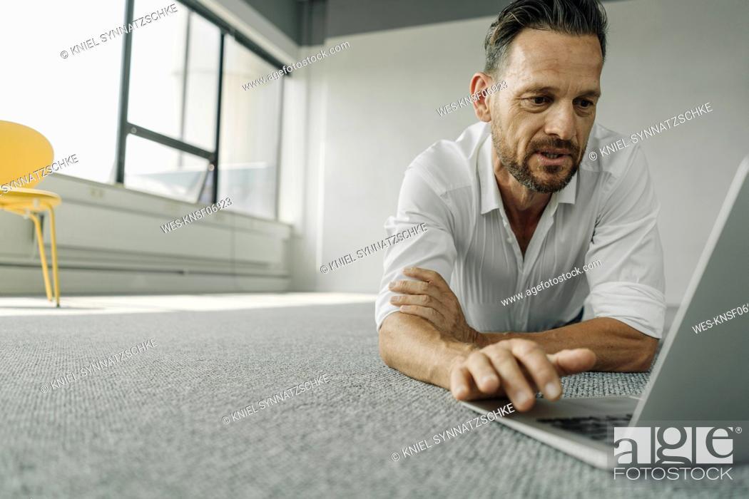 Photo de stock: Mature businessman lying on the floor in empty office using laptop.