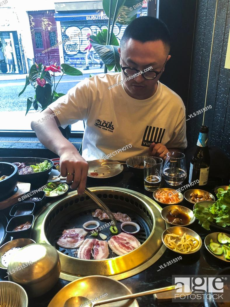 Imagen: paris, France, People Sharing Meals at Table, Grilling Food, in Korean Restaurant in Belleville Neighborhood 'Gangnam'. Chinese Tourist, (Model Released).